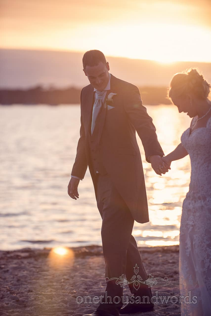 Couple walk on the beach at sunset from Harbour Heights wedding