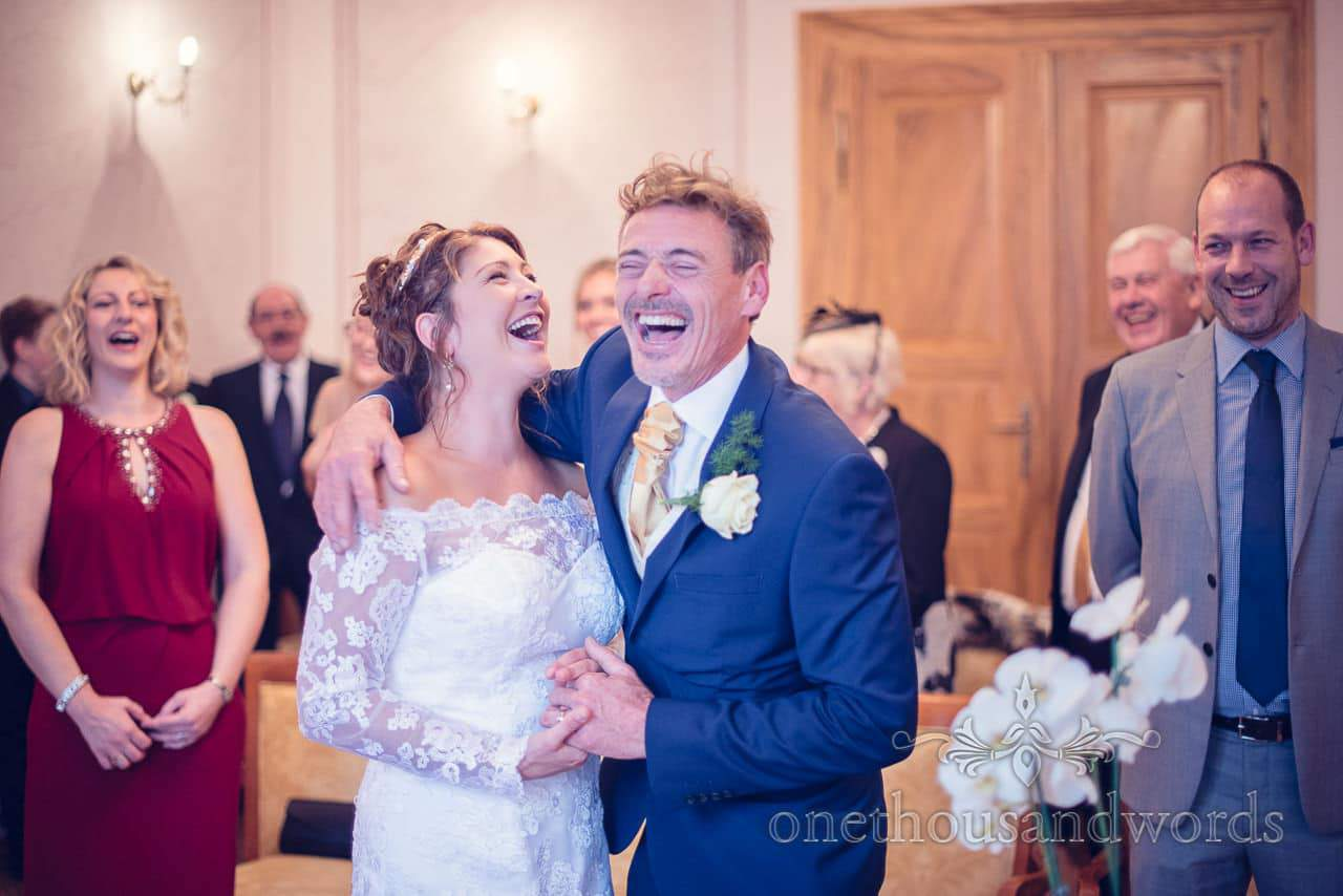 Destination wedding photographers capture bride and groom laughing at Bled wedding ceremony