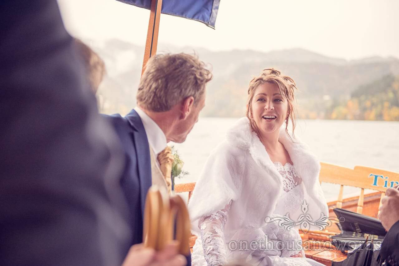 destination wedding photographers capture Bride on wooden boat in Lake Bled Slovenia
