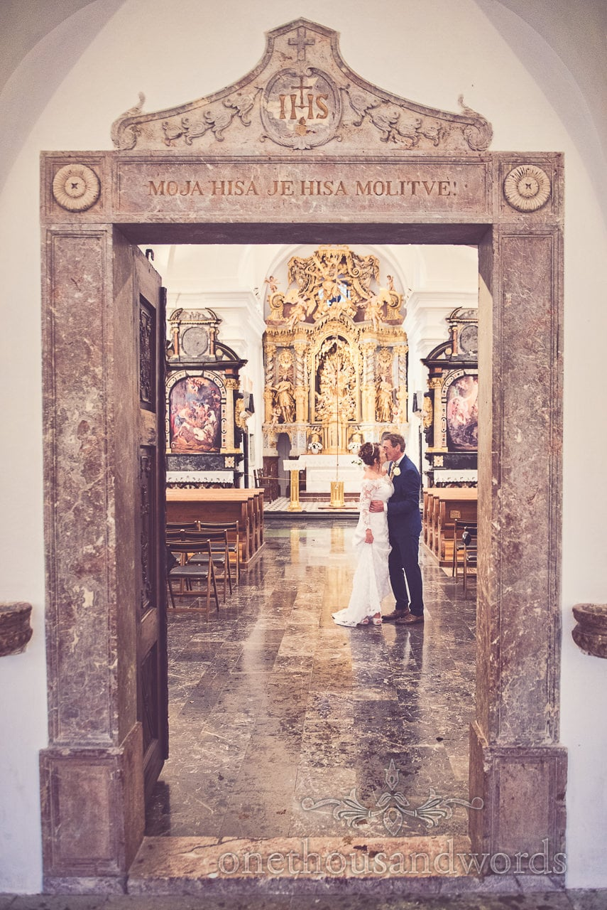 Destination wedding photographers photograph bride and groom kissing in Slovenian Church
