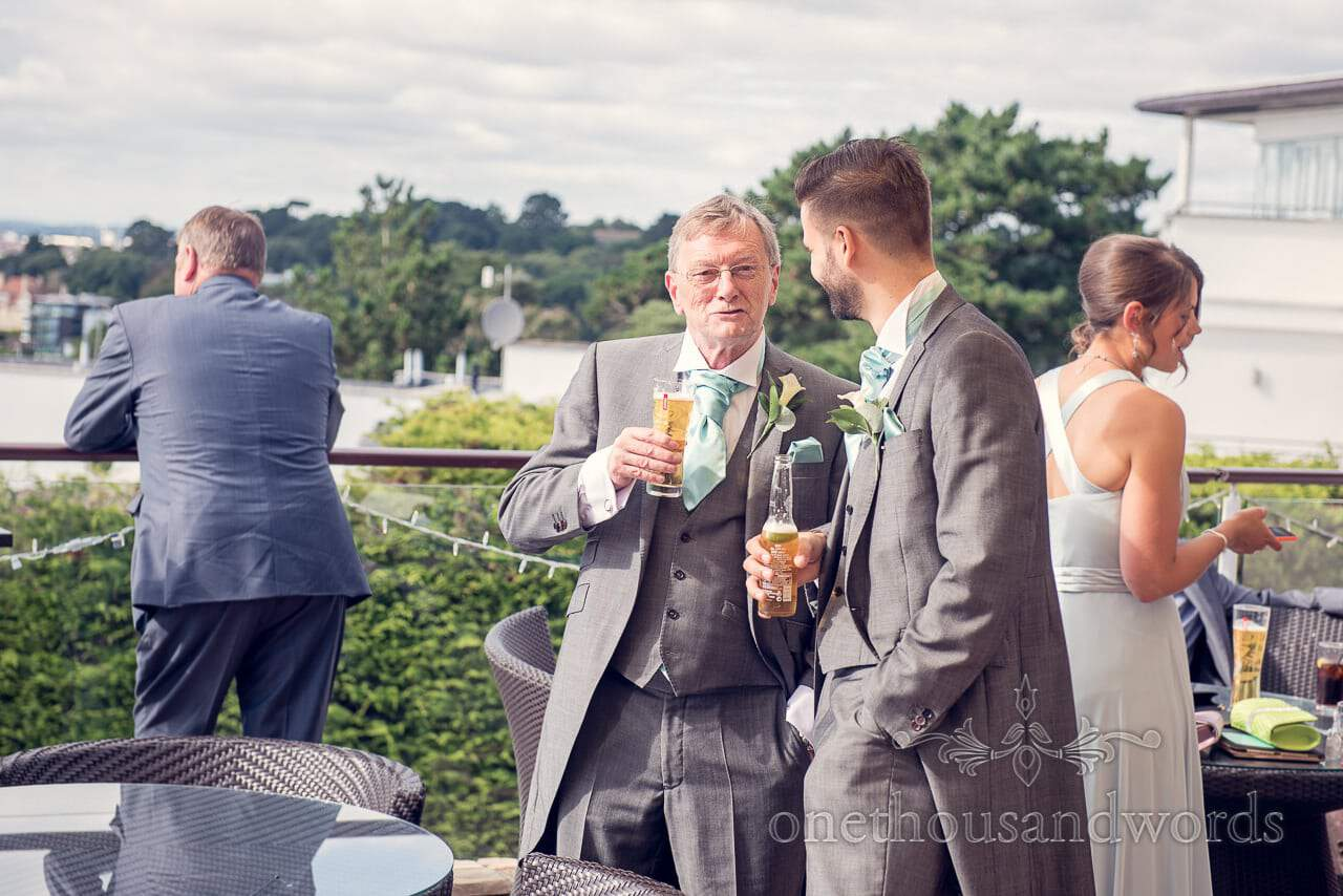 Father of the bride and usher enjoy a drink at Harbour Heights outdoor wedding