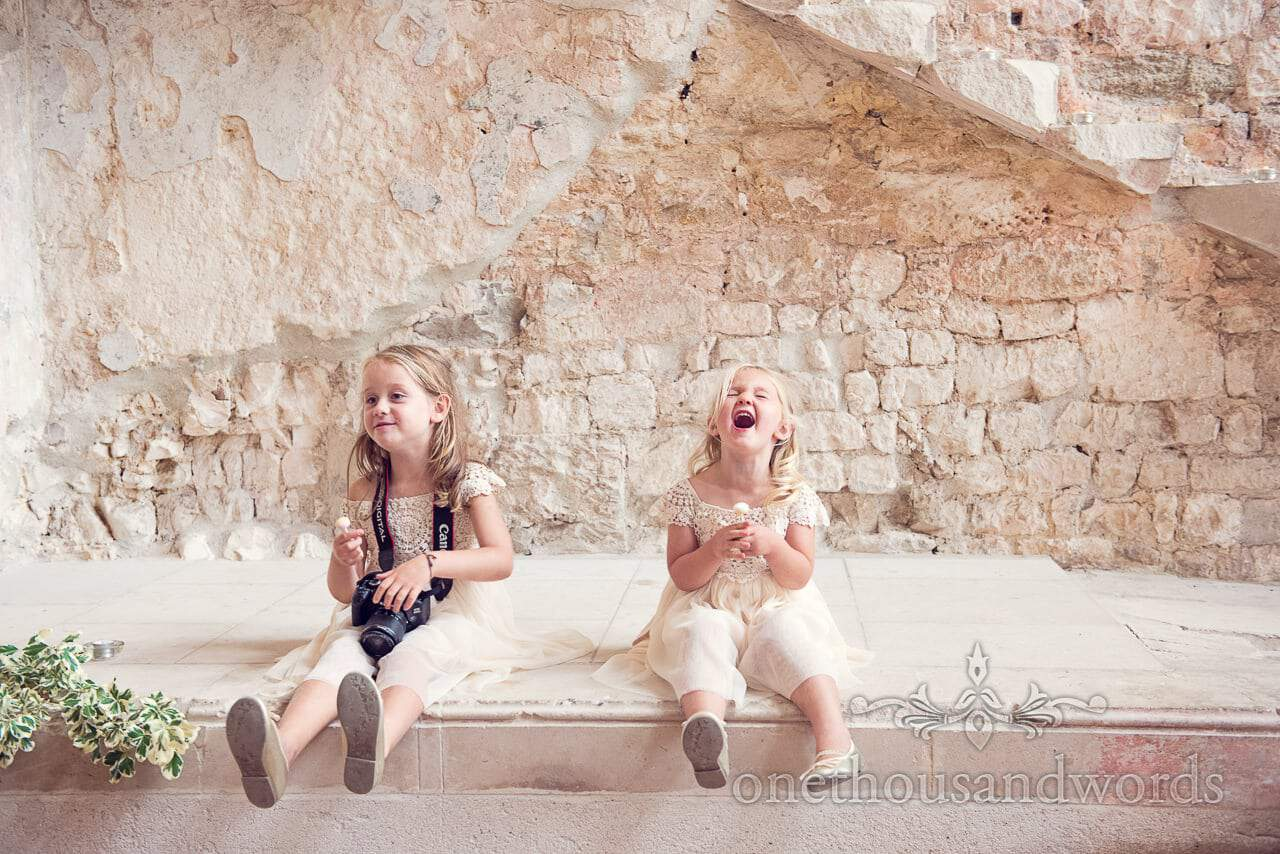 Flowergirls laughing by light stone wall at Lulworth castle wedding venue in Dorset