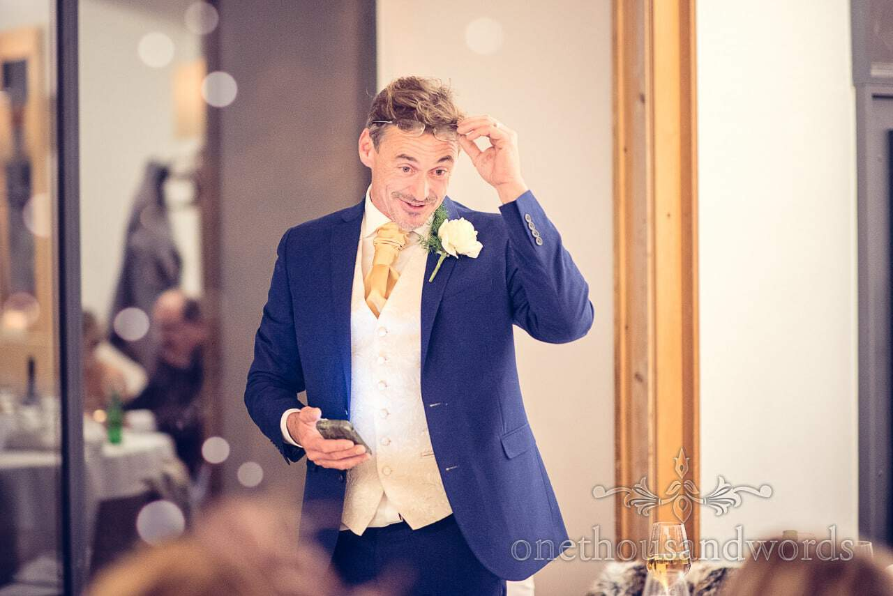 Groom in blue suit and gold tie adjusts reading glasses during wedding speech