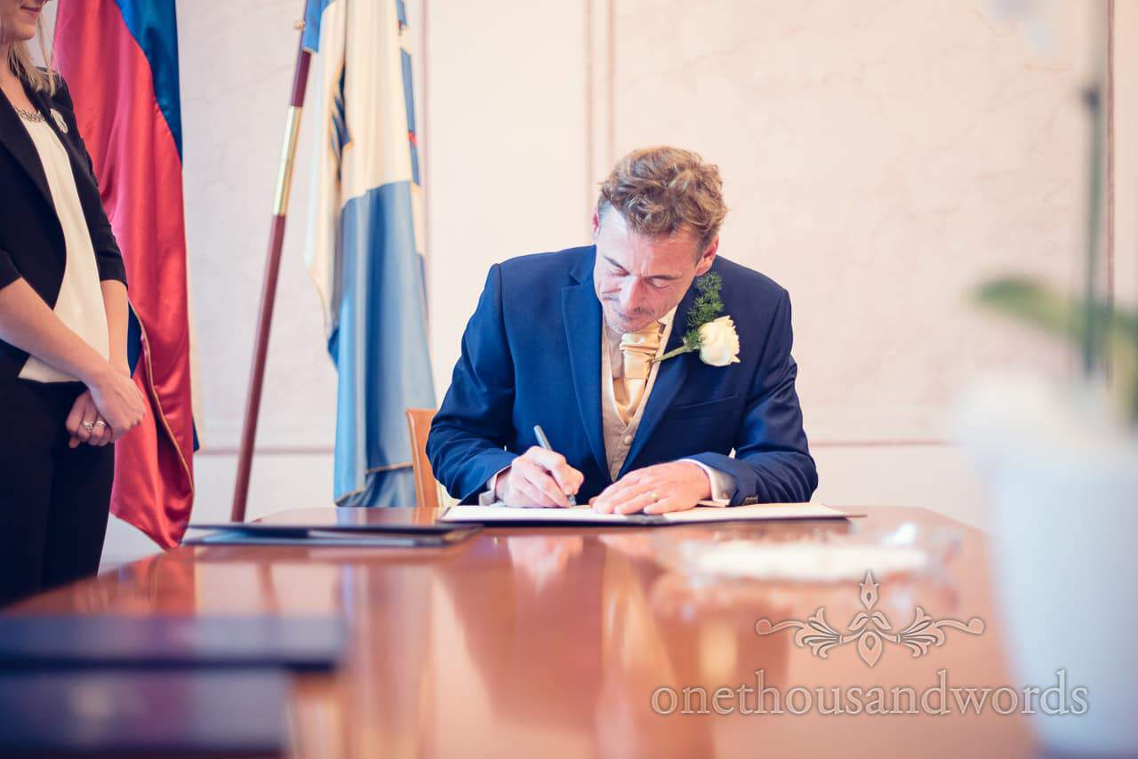Groom in blue suit signs the register of marriages in Bled Town Hall wedding