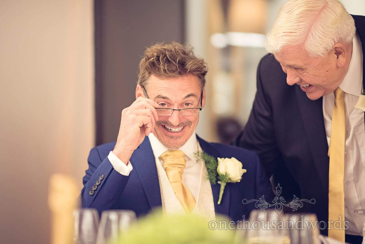 Groom tries on his reading glasses at Castle Bled wedding breakfast