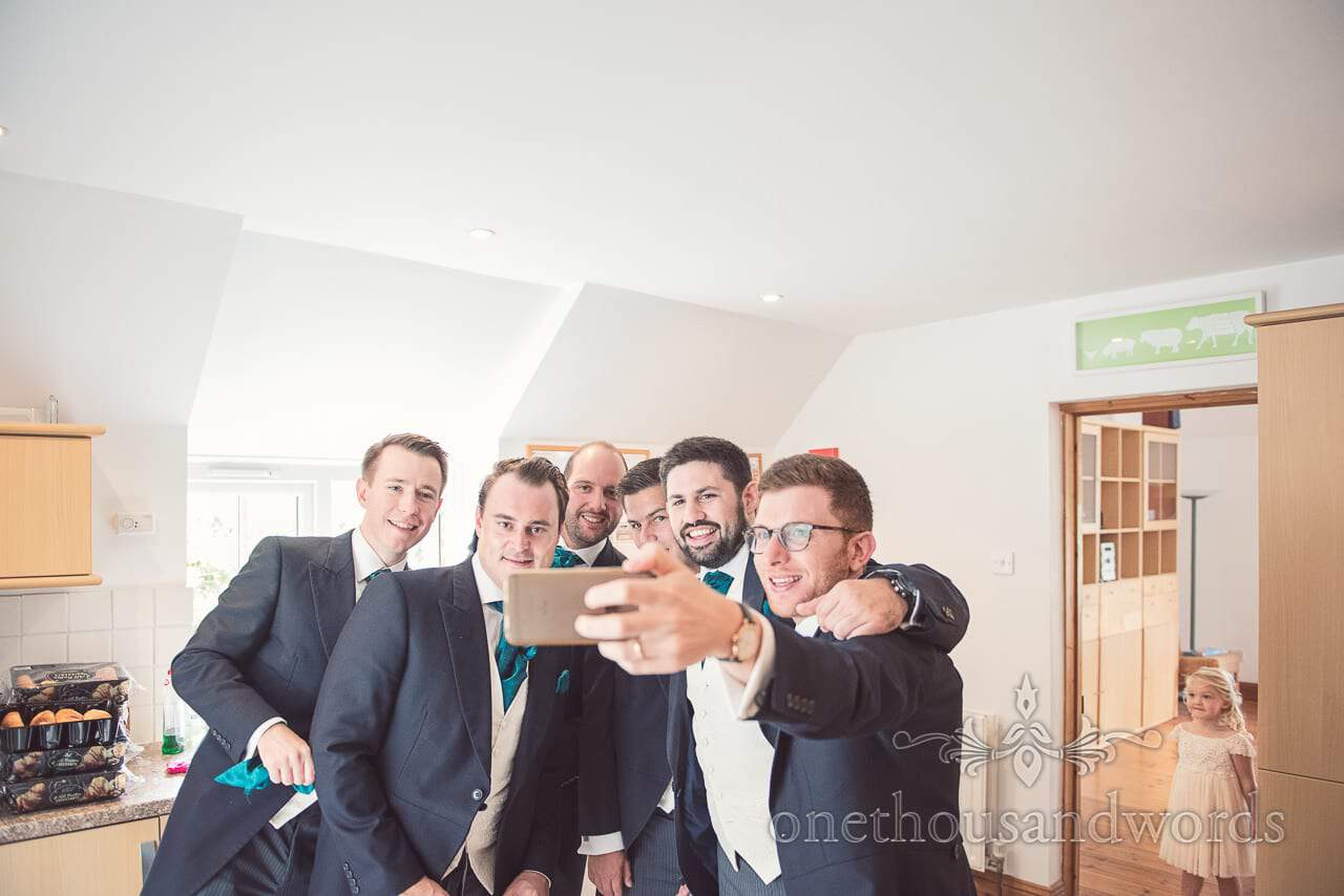 Groomsmen in green cravates take wedding morning selfie watched by flowergirl