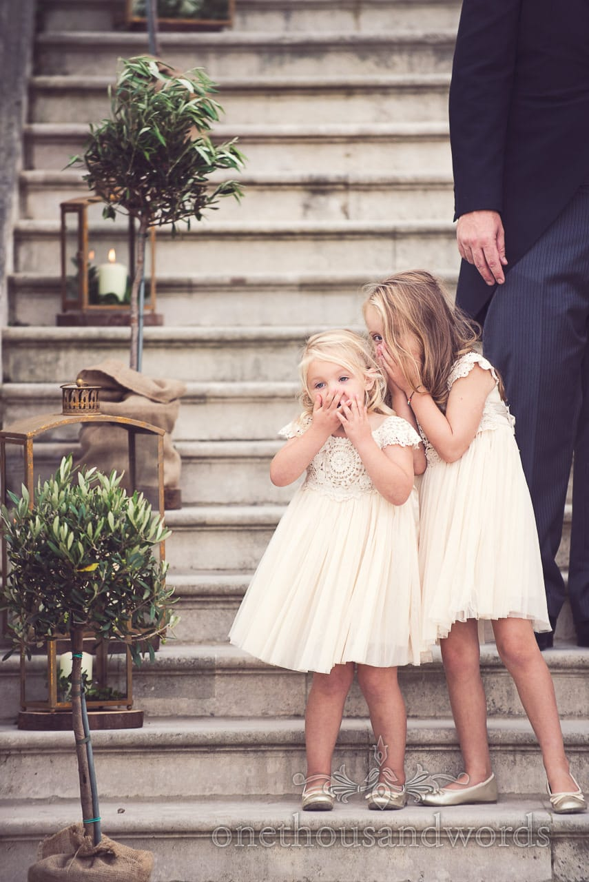 Naughty flower girls on stone steps during Lulworth castle wedding group photographs
