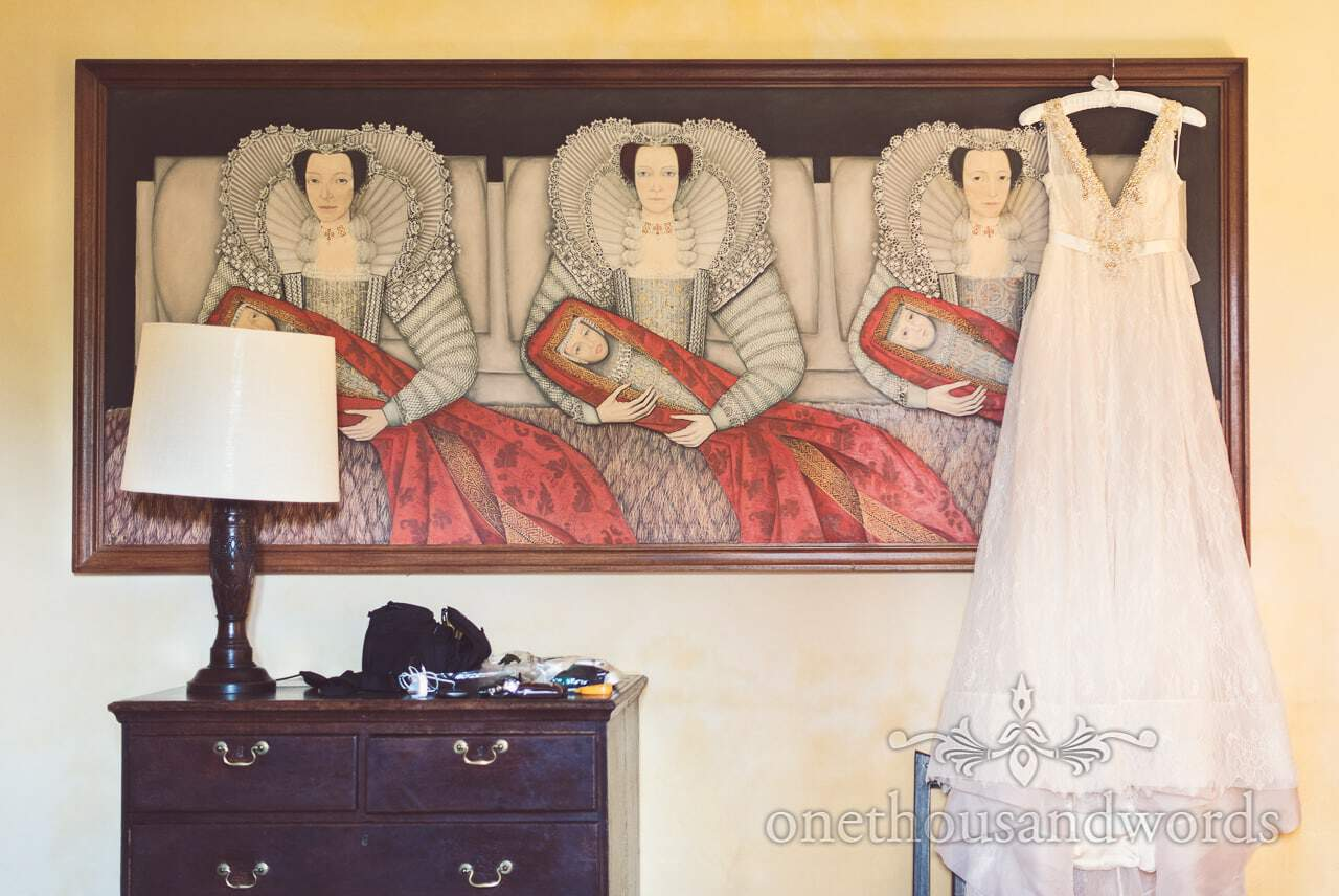 Wedding dress hangs with old painting at Dorset Castle Wedding best wedding photos