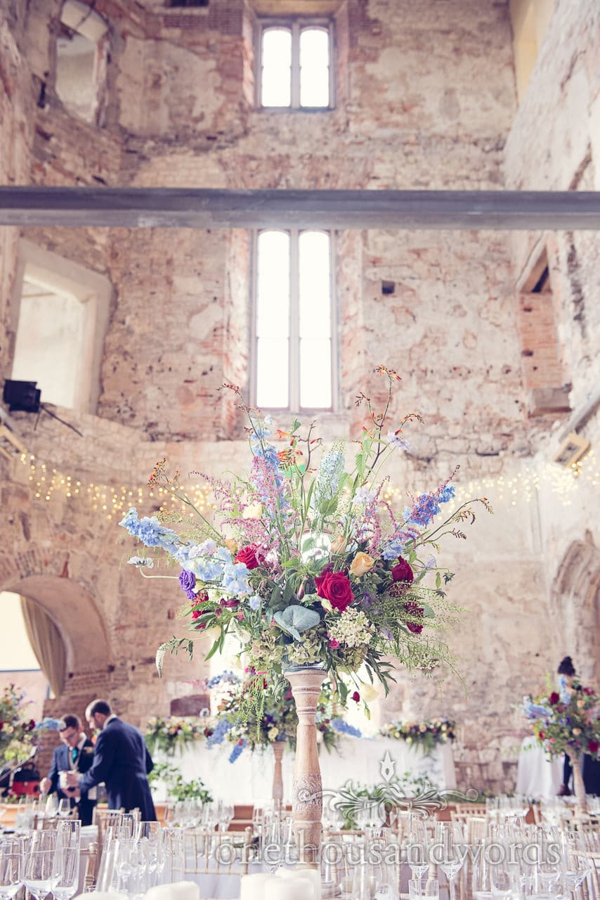 Wedding flowers in wooden candle stick at Lulworth Castle wedding venue in Dorset