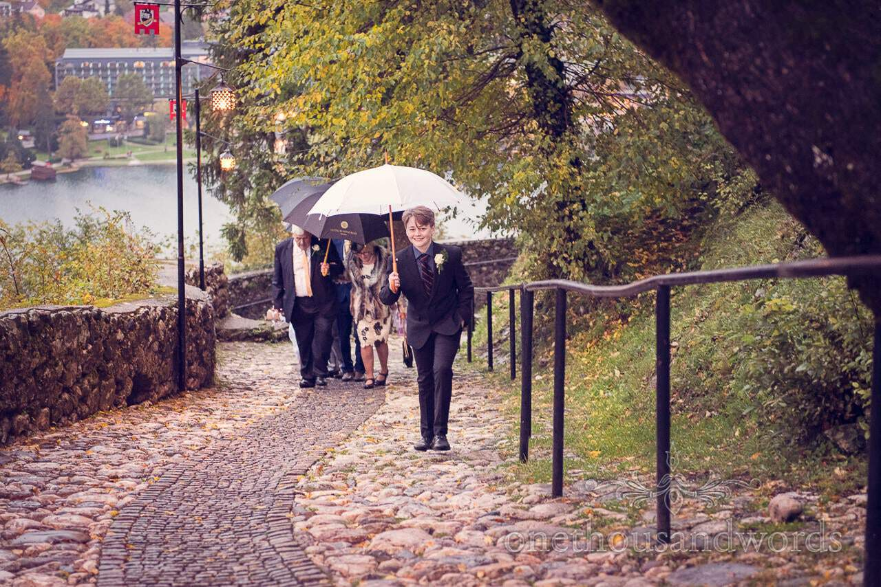 Wedding guests walk up steep cobbled path to Bled Castle in Slovenia