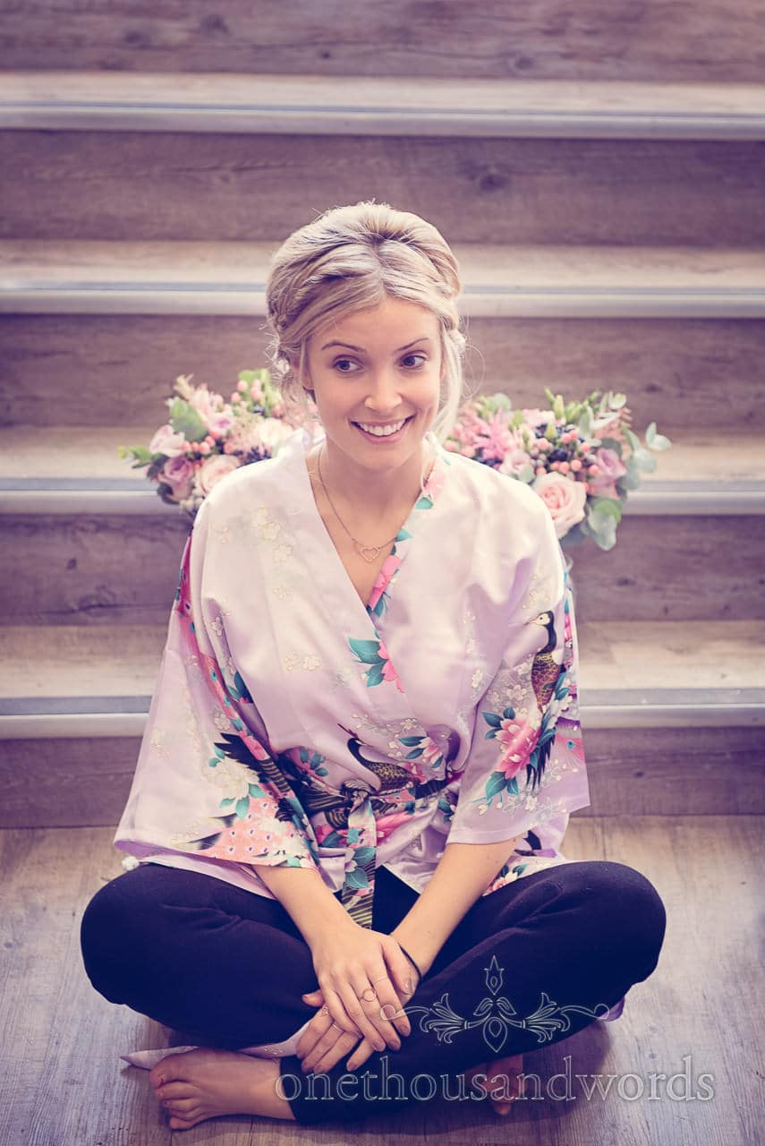 Beautiful blonde bridesmaid in silk kimono peacock design dressing gown with floral wings
