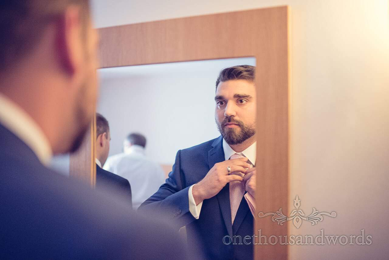 Best man in blue wedding suit and pink tie looks in mirror on wedding morning