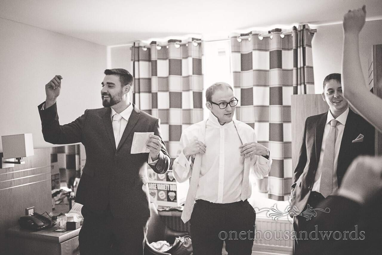 Black and white wedding photograph of groom and groomsmen wedding preparations