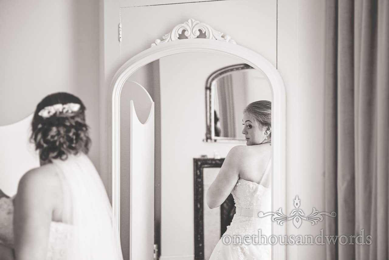 Black and white wedding portrait photograph of bride looking at her dress in mirror