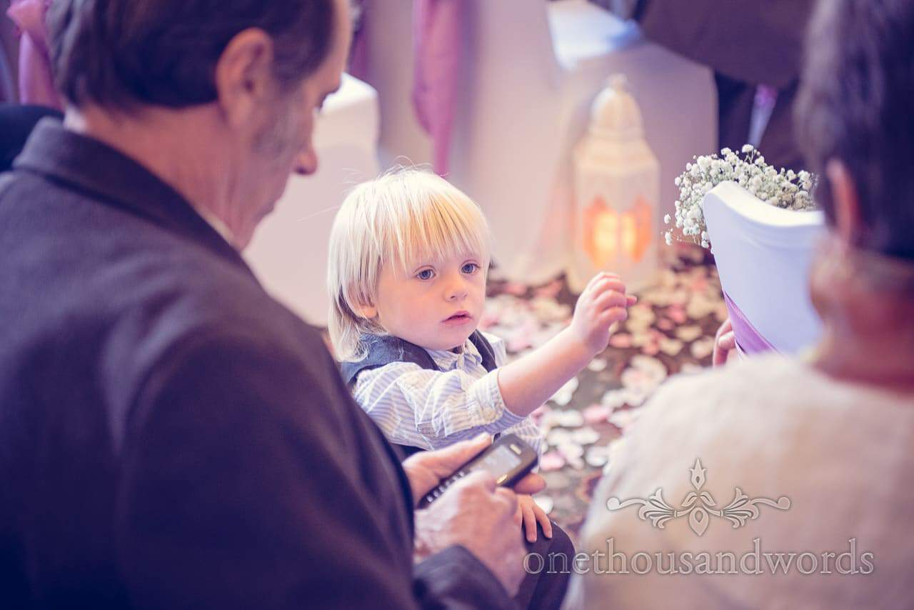 Blonde child examines the wedding aisle flowers at Northcote House wedding