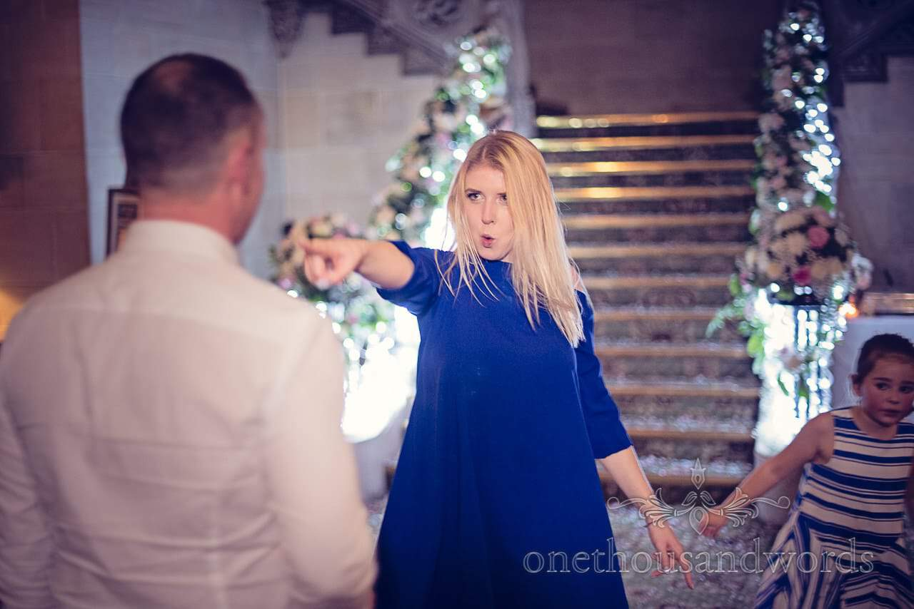 Blonde wedding guest dances infront of staircase at Northcote House wedding