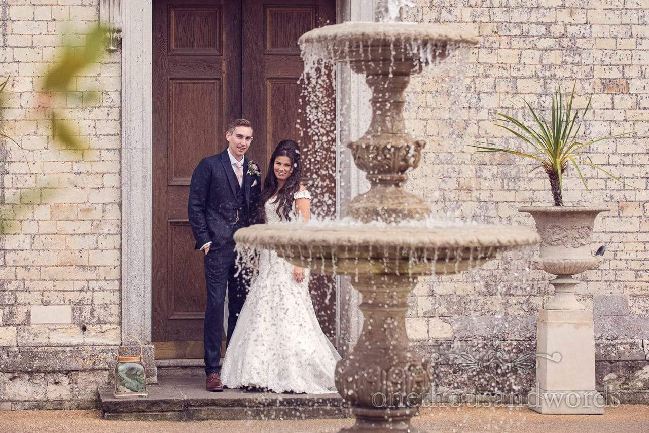 Bride and groom at front door with fountain at Froyle Park wedding photographs