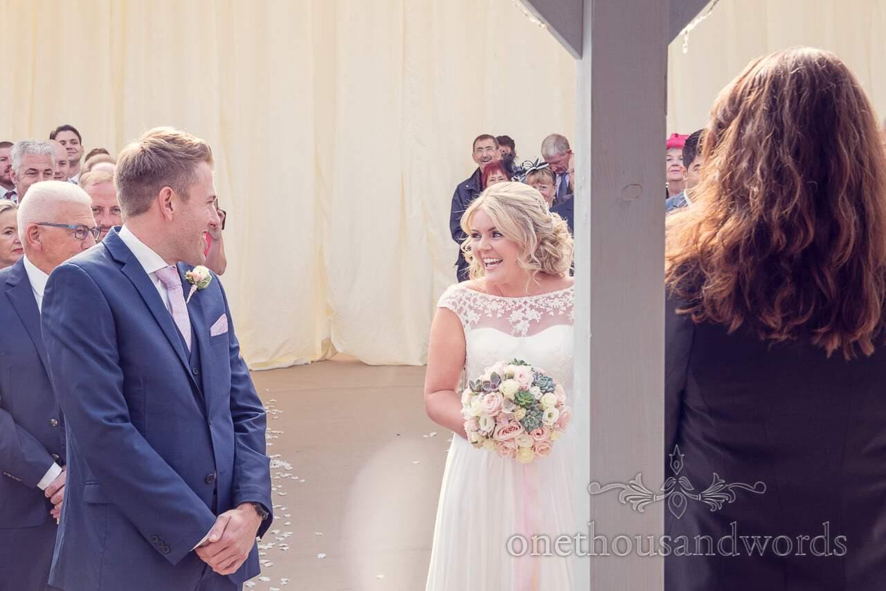 Bride and groom exchange looks at Holme for Gardens Dorset wedding