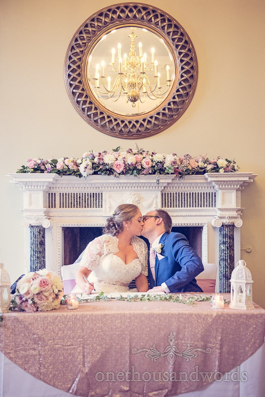 Bride and groom kiss as they sign the register at Northcote House wedding