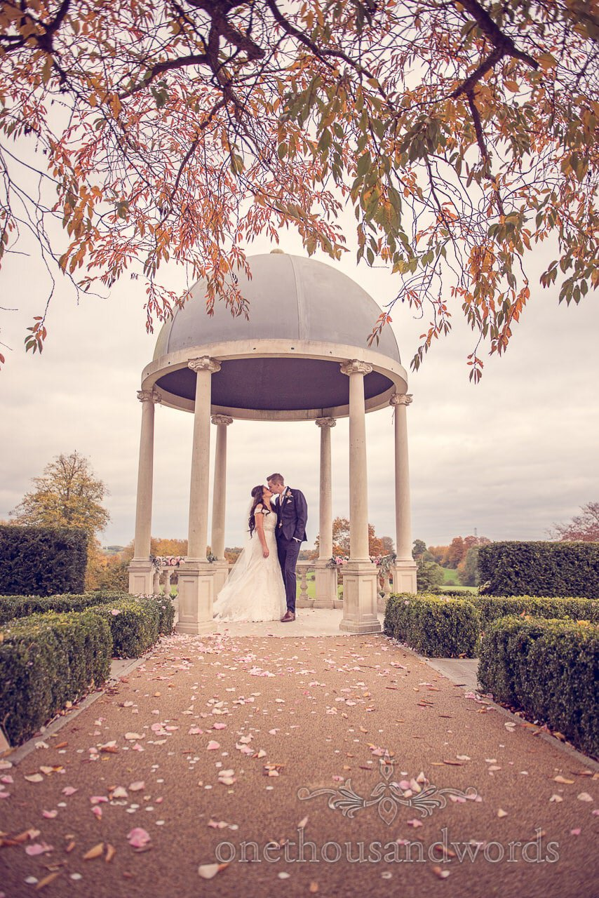 Bride and groom kiss under pagoda at Froyle Park wedding photographs