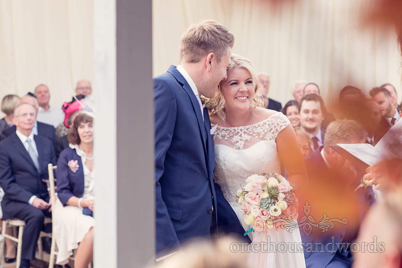 Bride and groom laugh during ceremony at Holme for Gardens Dorset wedding