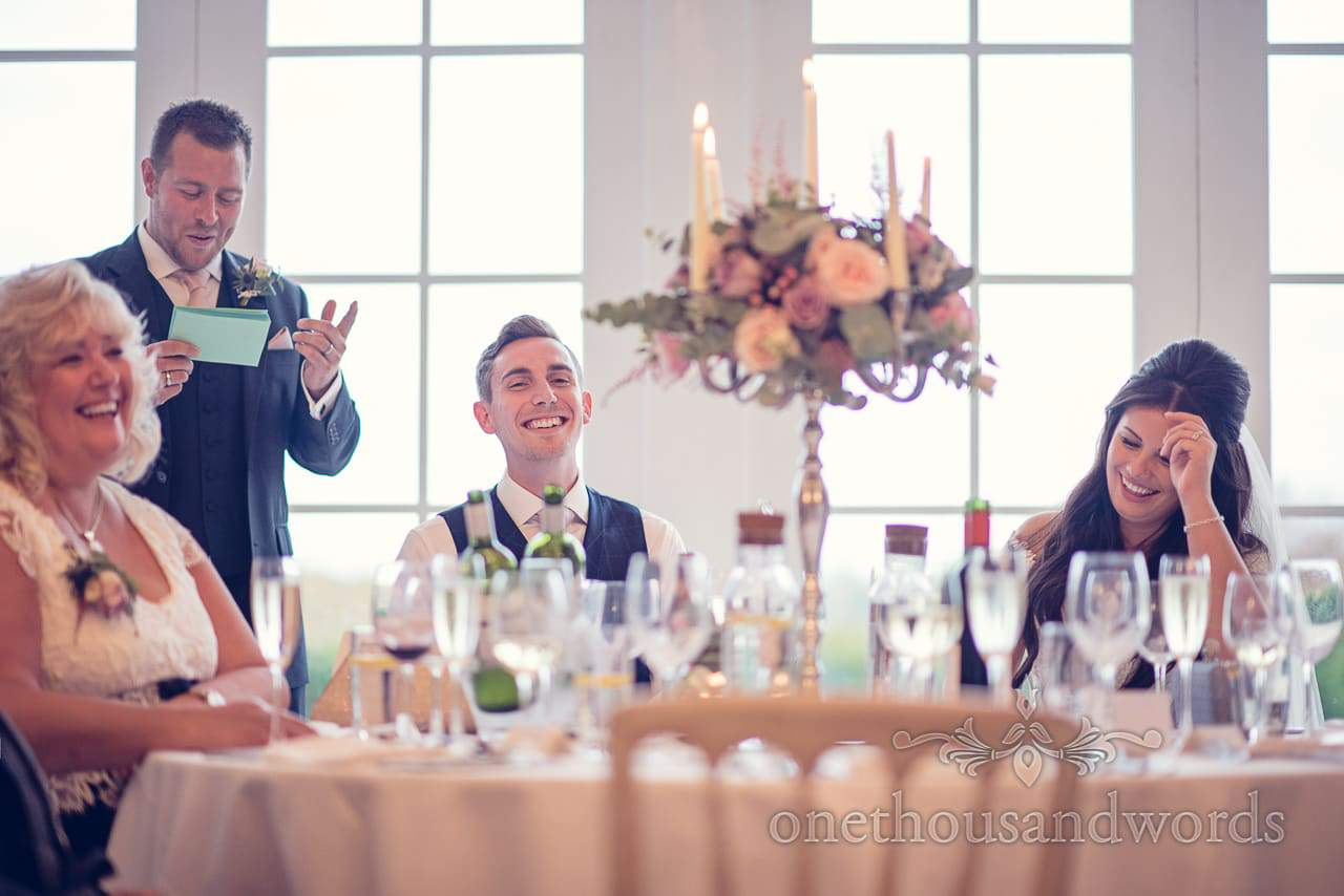 Bride and groom react to best mans speech at Froyle Park wedding photographs