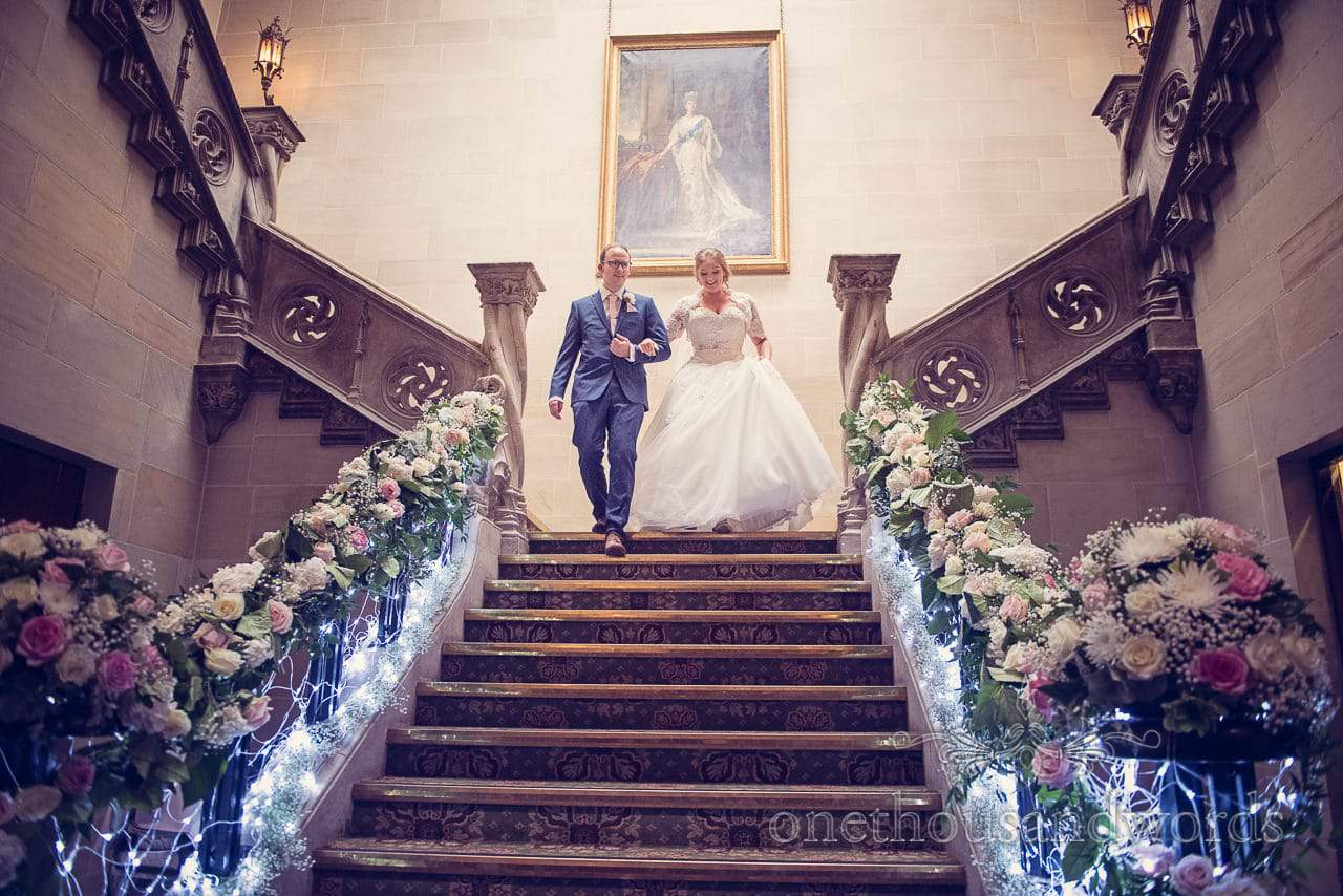 Bride and groom walk down grand stone staircase at Northcote House wedding photographs