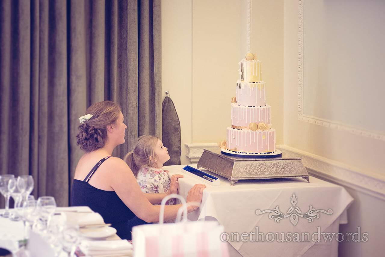 Bride and her daughter look at four tier pink and gold wedding cake on wedding morning