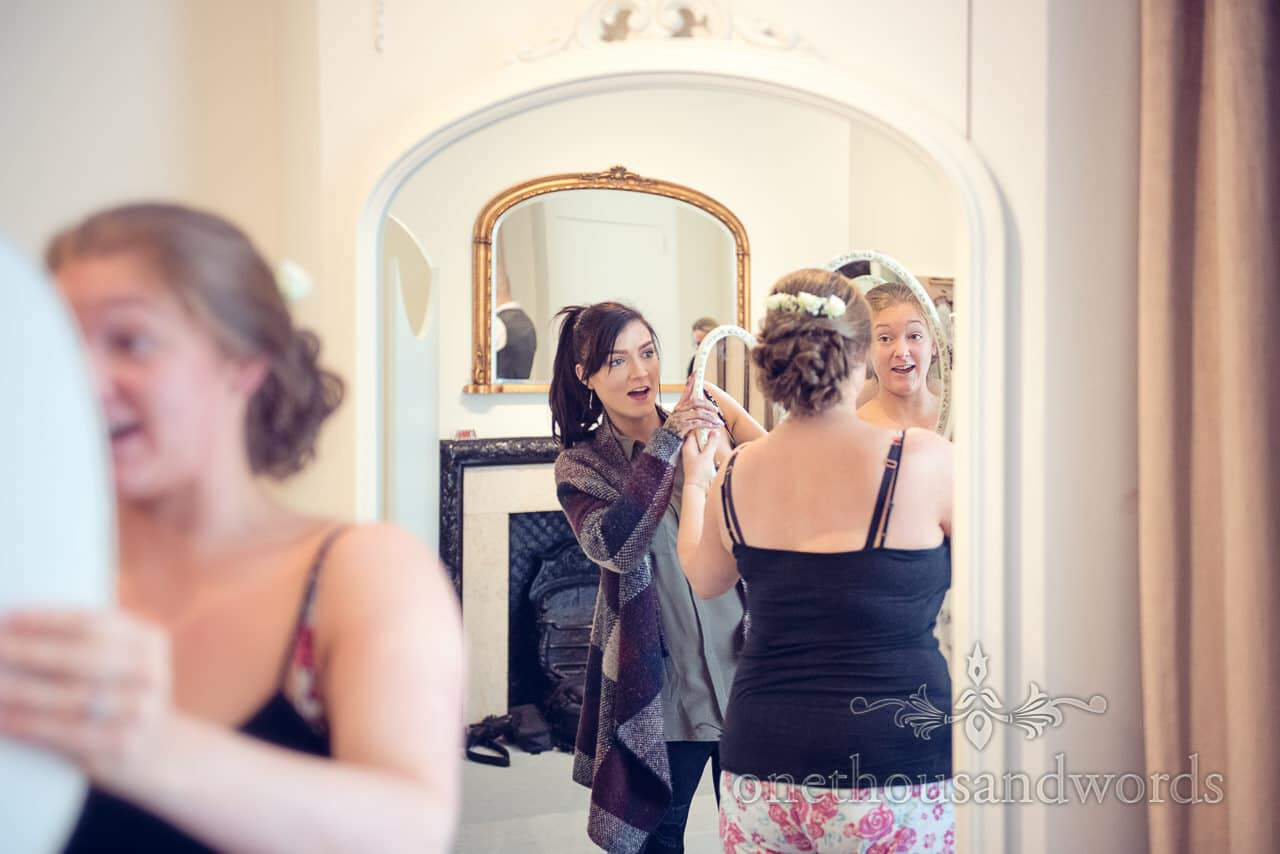 Bride and wedding hairdresser look ar hair in many mirrors at Northcote House wedding