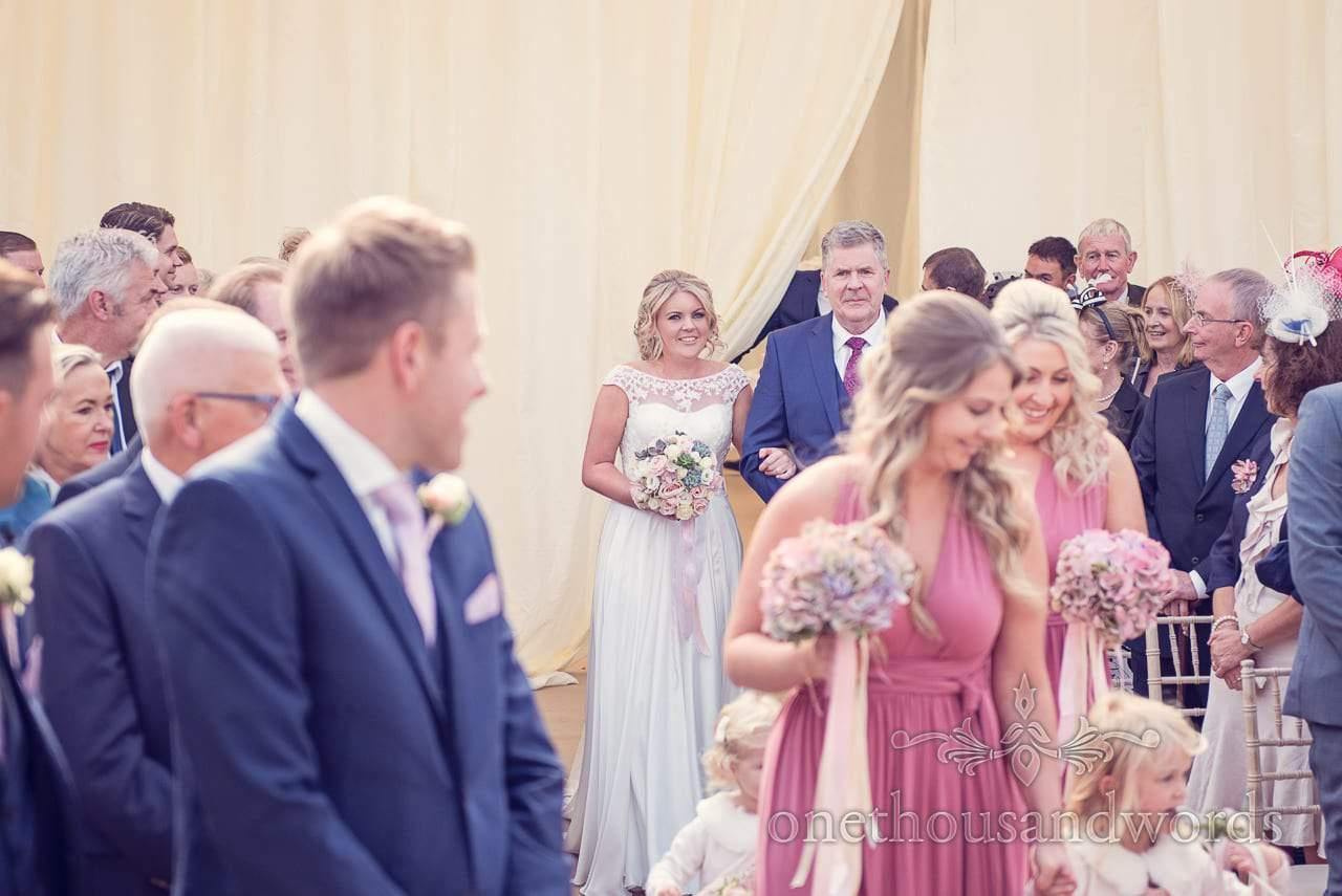 Bride comes down the aisle at Holme for Gardens Dorset wedding