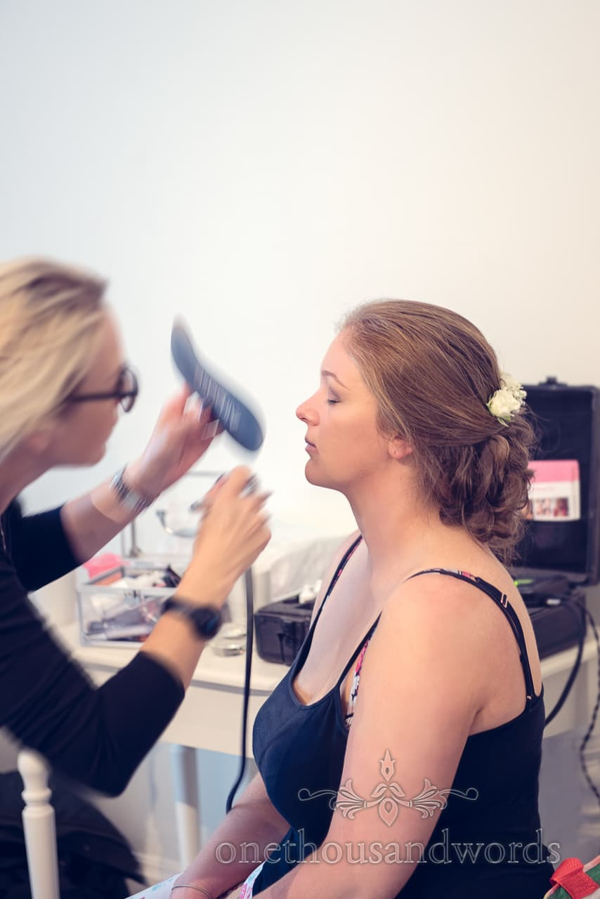 Bride has makeup sprayed on by MUA on Northcote House wedding morning
