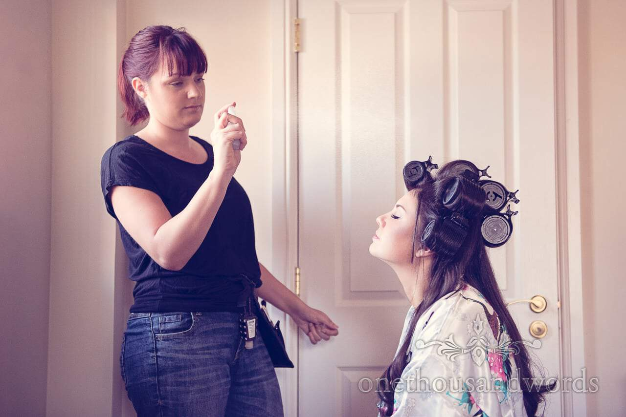 Bride in curlers and silk kimono has wedding makeup fiked by wedding MUA at Froyle Park