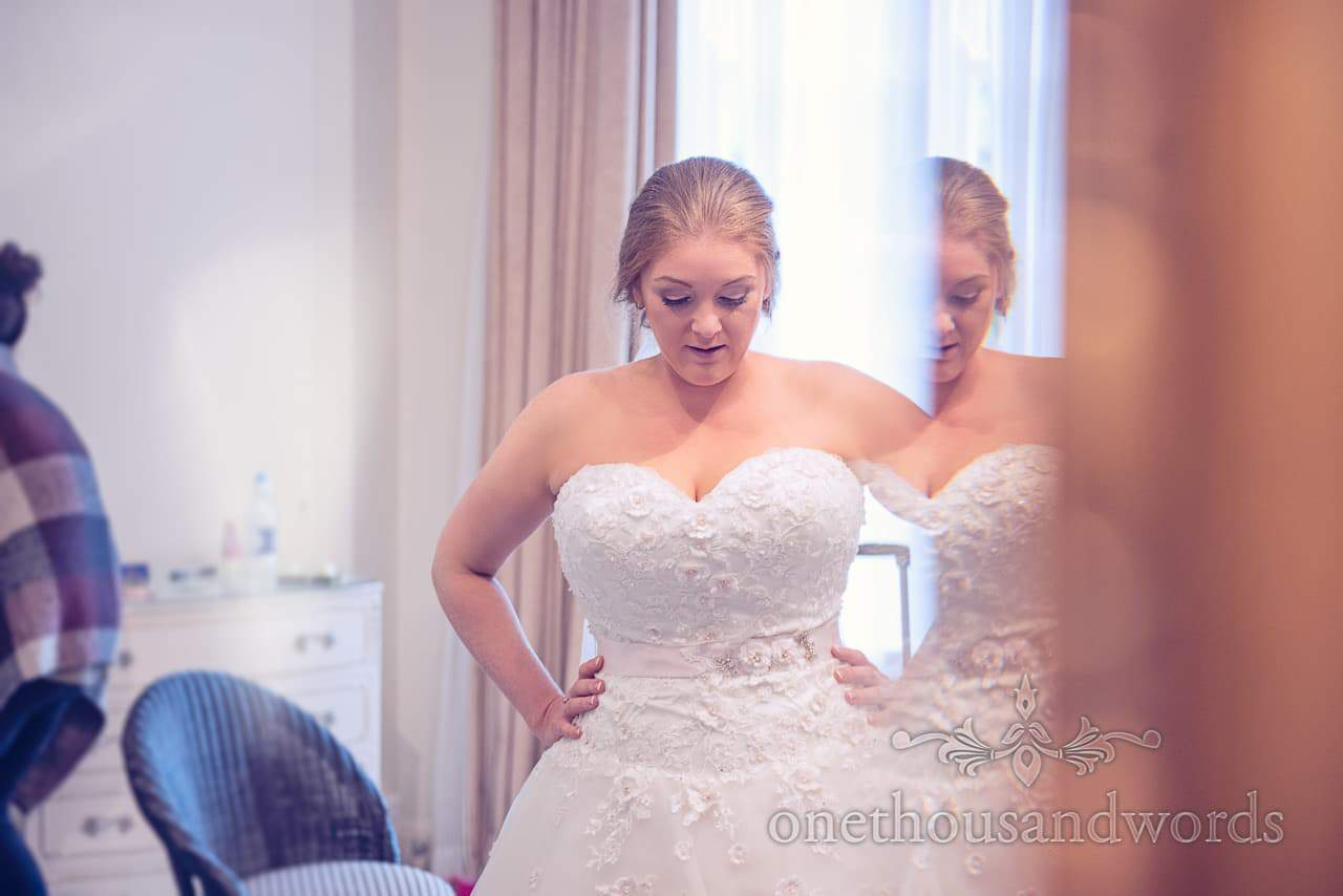 Bride in sleaveless love heart neckline dress in mirror on wedding morning