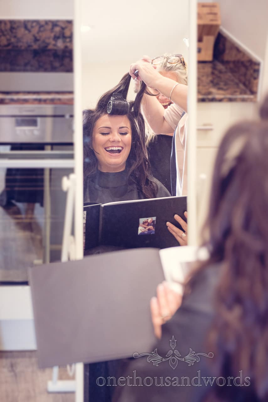 Bride laughs at photo book present in mirror whilst having her wedding hair styled
