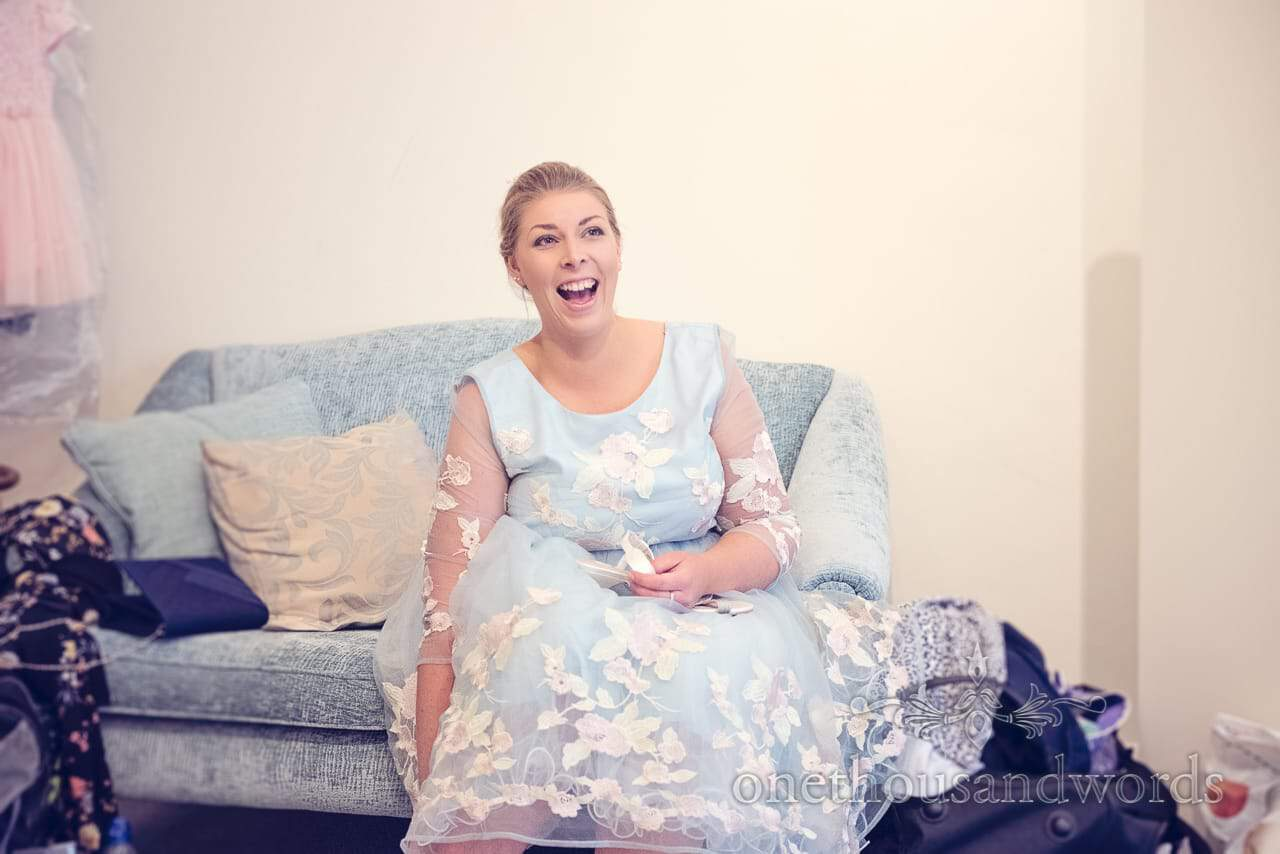 Bridesmaid in pale blue flower patterned bridesmiad dress laughs on wedding morning