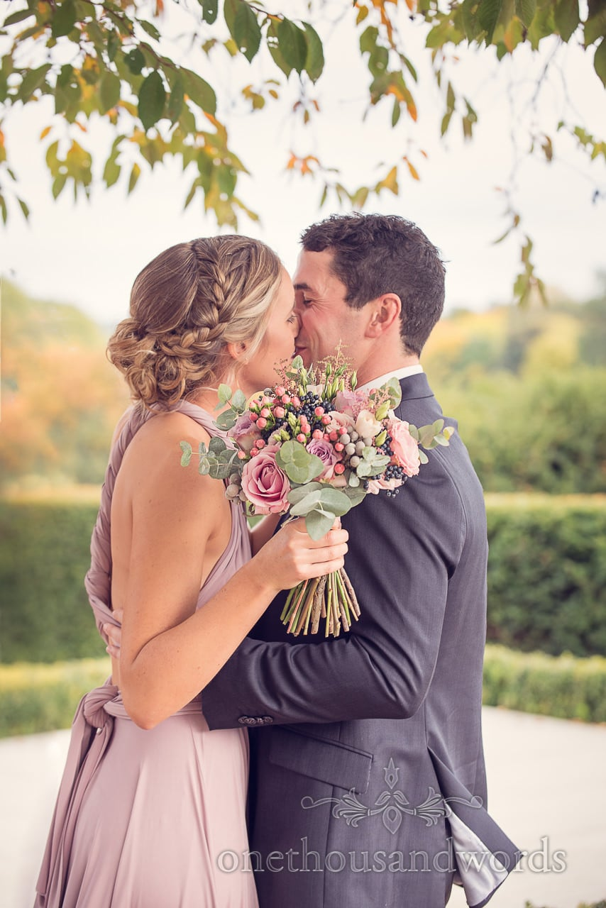 Bridesmaid kisses partner at Froyle Park wedding photographs