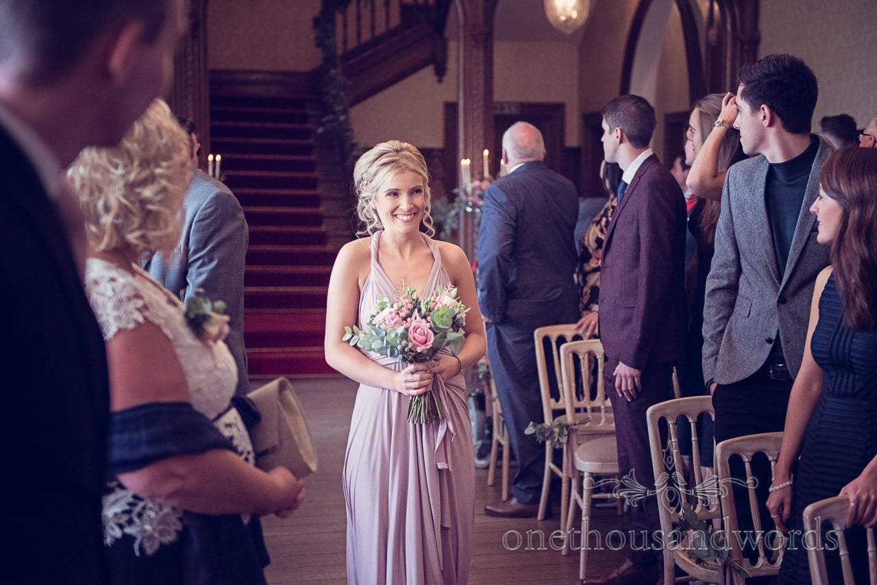 Bridesmaid walks down the aisle at Froyle Park wedding photograph