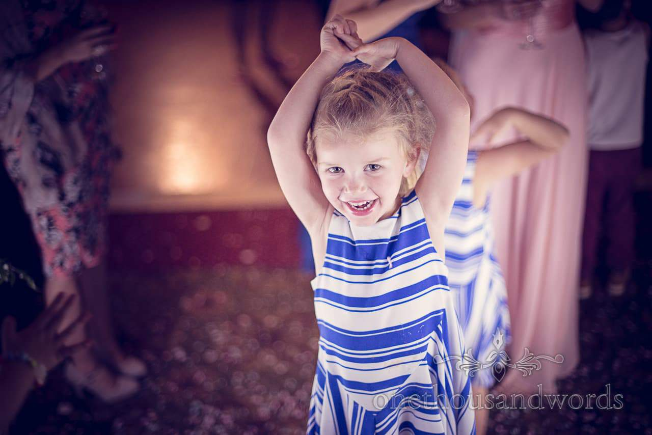 Child wedding guest in stripey blue outfit dancing at Northcote house wedding