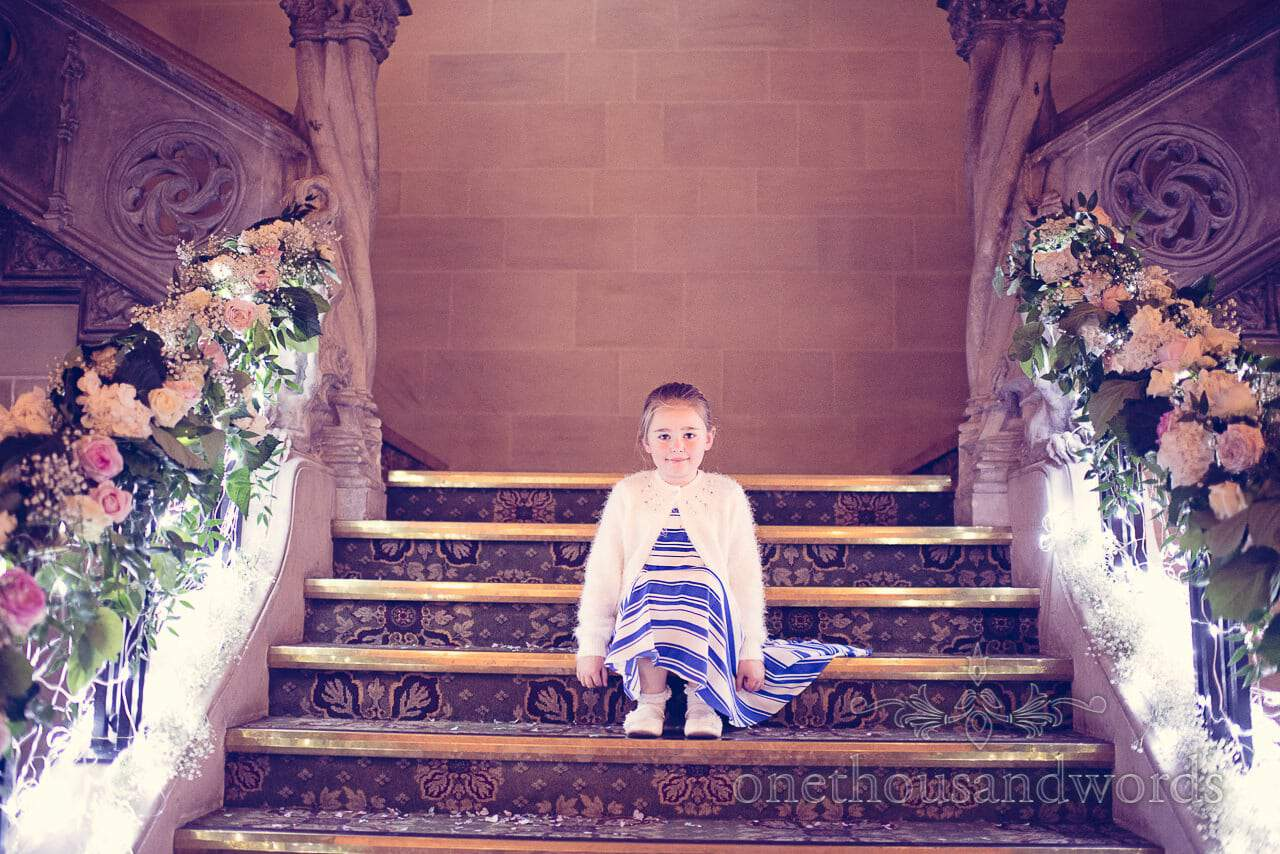 Child wedding guest on grand stair case with flowers and fairy lights at Northcote House