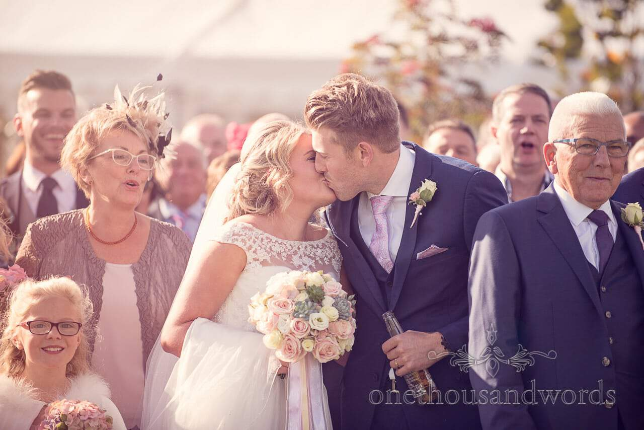 Couple kiss during group photo at Holme for Gardens Dorset wedding