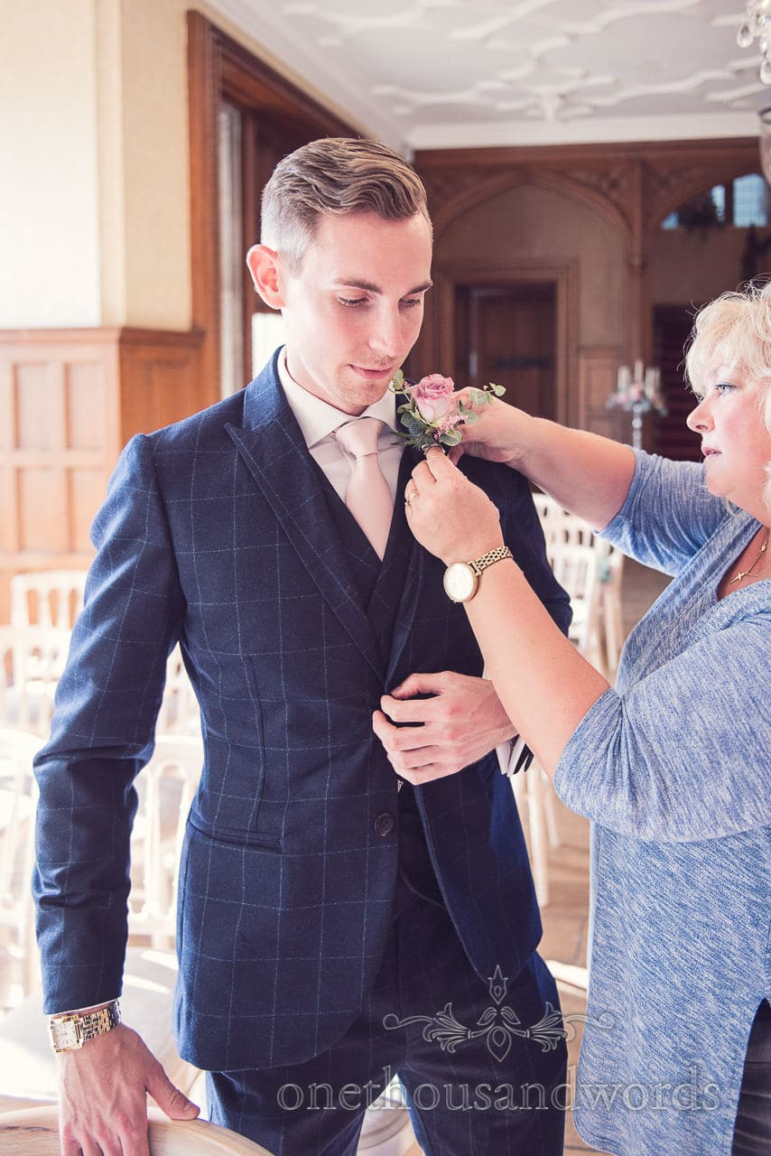 Dapper groom in custom made blue wedding suit has wedding button hole correctly placed