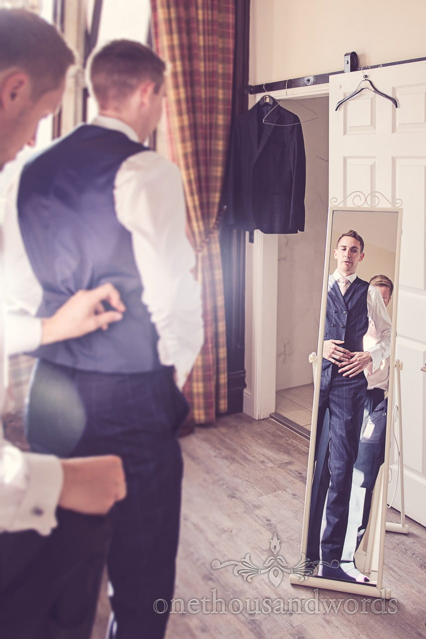 Dapper groom with custom blue wedding suit in full length mirror at Froyle Park wedding