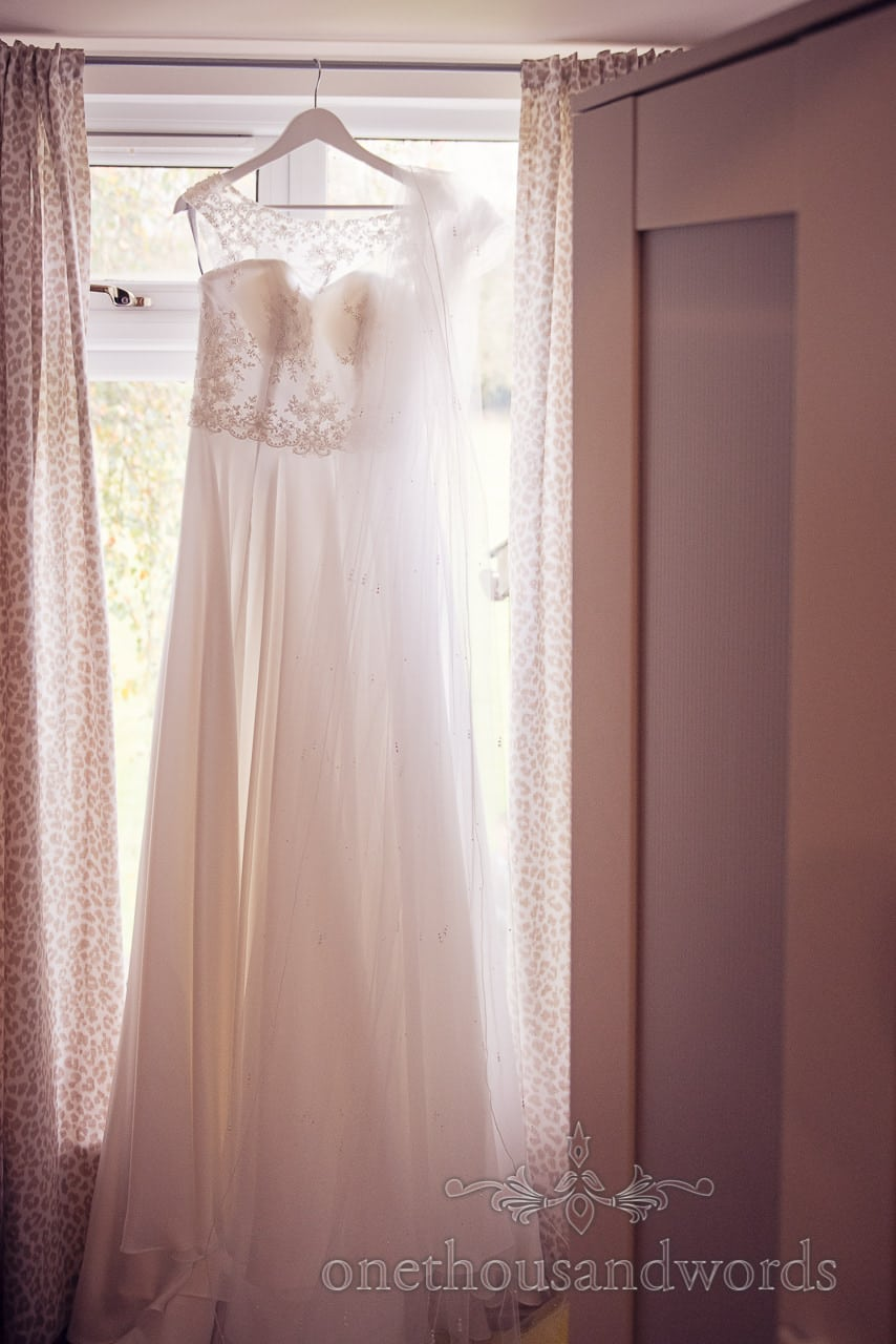 Dress hangs in window before Holme for Gardens wedding