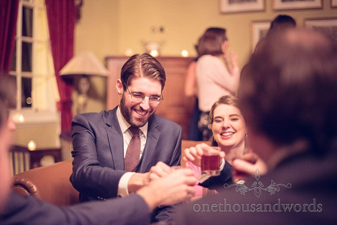 Evening wedding guest cheers with drinks from Nothcote House wedding photographs
