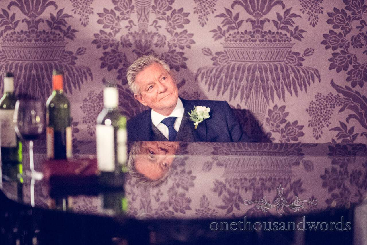 Father of the groom at the piano at Froyle Park wedding photographs