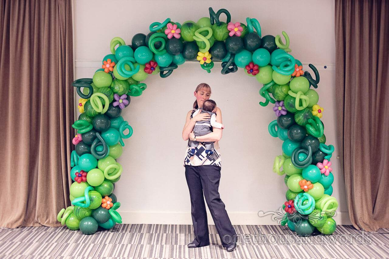 Floral green balloon archway with wedding child care worker rocking baby at wedding