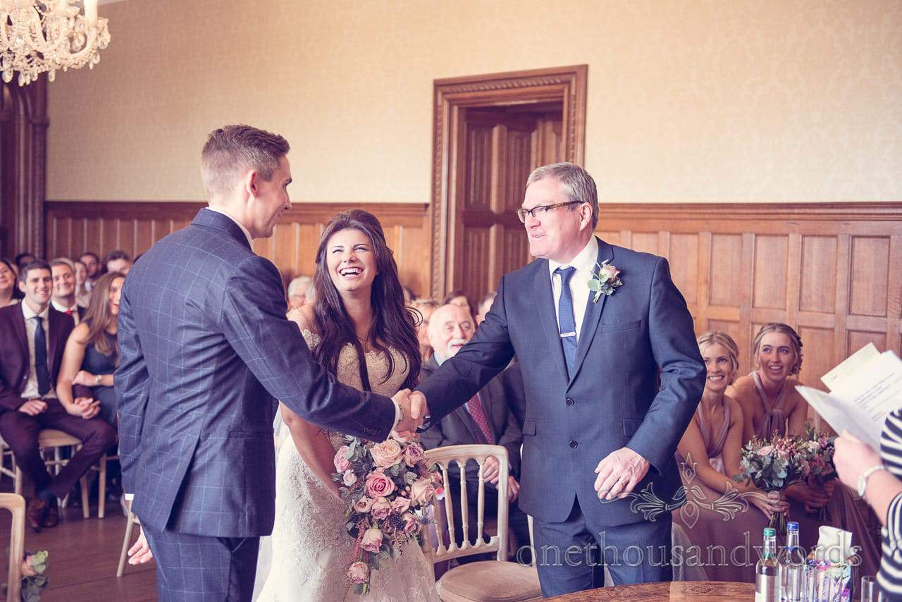 Groom and brides father shake on it at Froyle Park wedding photographs