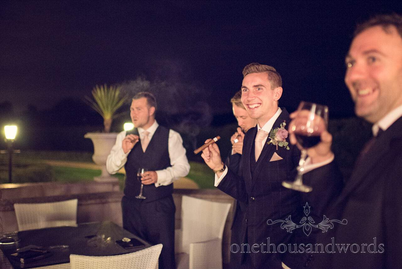 Groom and groomsmen smoke cigars from Froyle Park wedding photographs