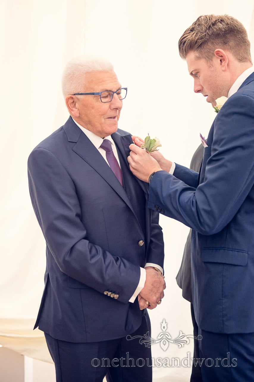 Groom helps father with buttonhole at Holme for Gardens Dorset wedding