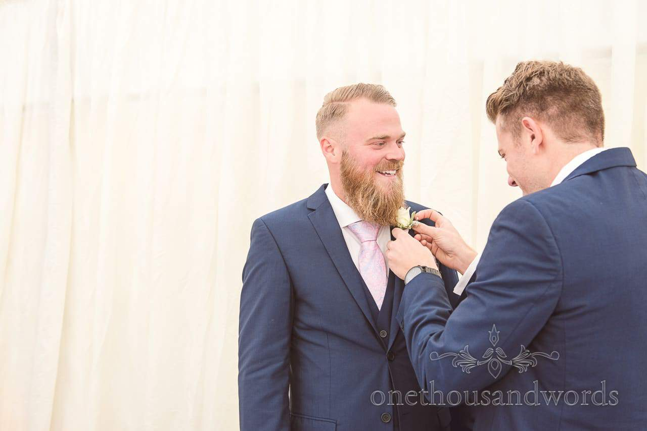 Groom helps groomsman with buttonhole at Holme for Gardens wedding